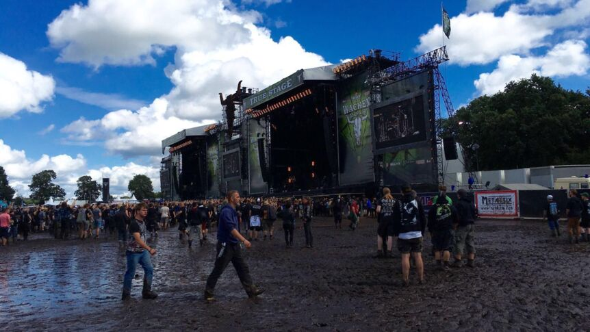 Festivalbesucher waten beim Wacken Open Air 2016 durch Matsch.