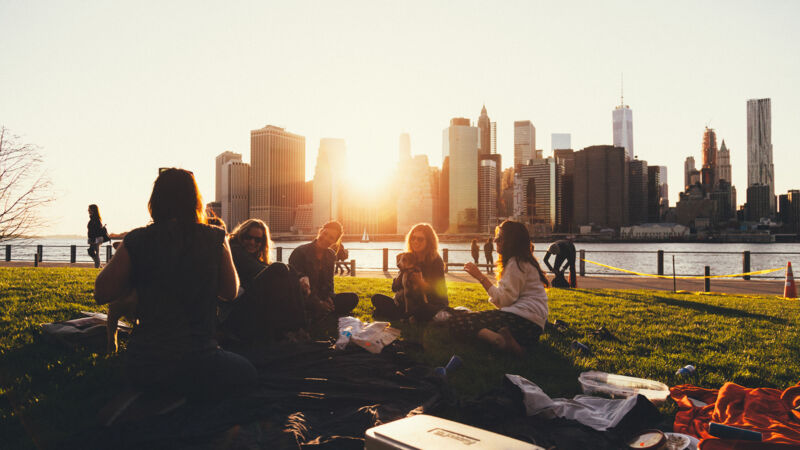 Freunde sitzen im Brooklyn Bridge Park in New York